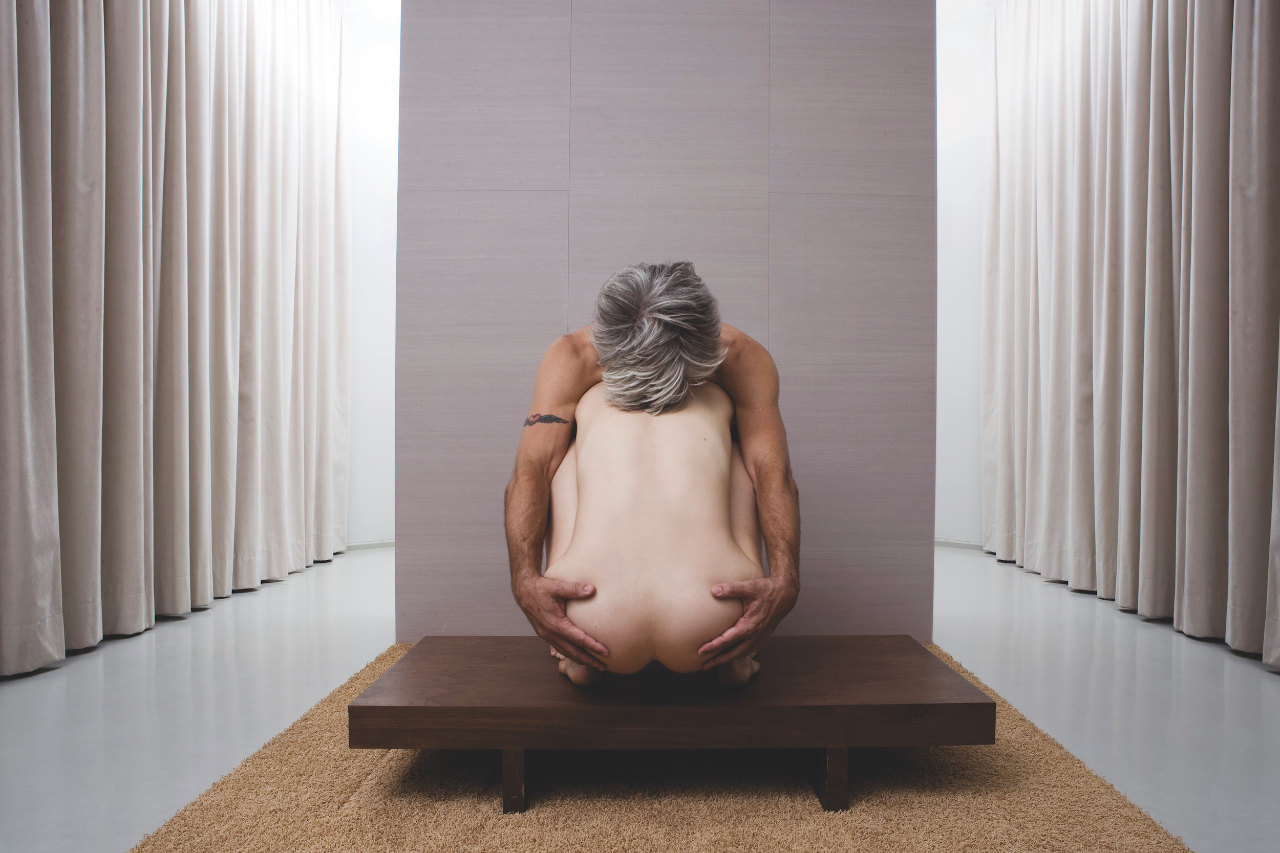 Curtis' arms and head (face hidden) frame Scaroni's back, as she squats on a short wooden platform in a beige curtained room. (photo: Sven Hagolani)