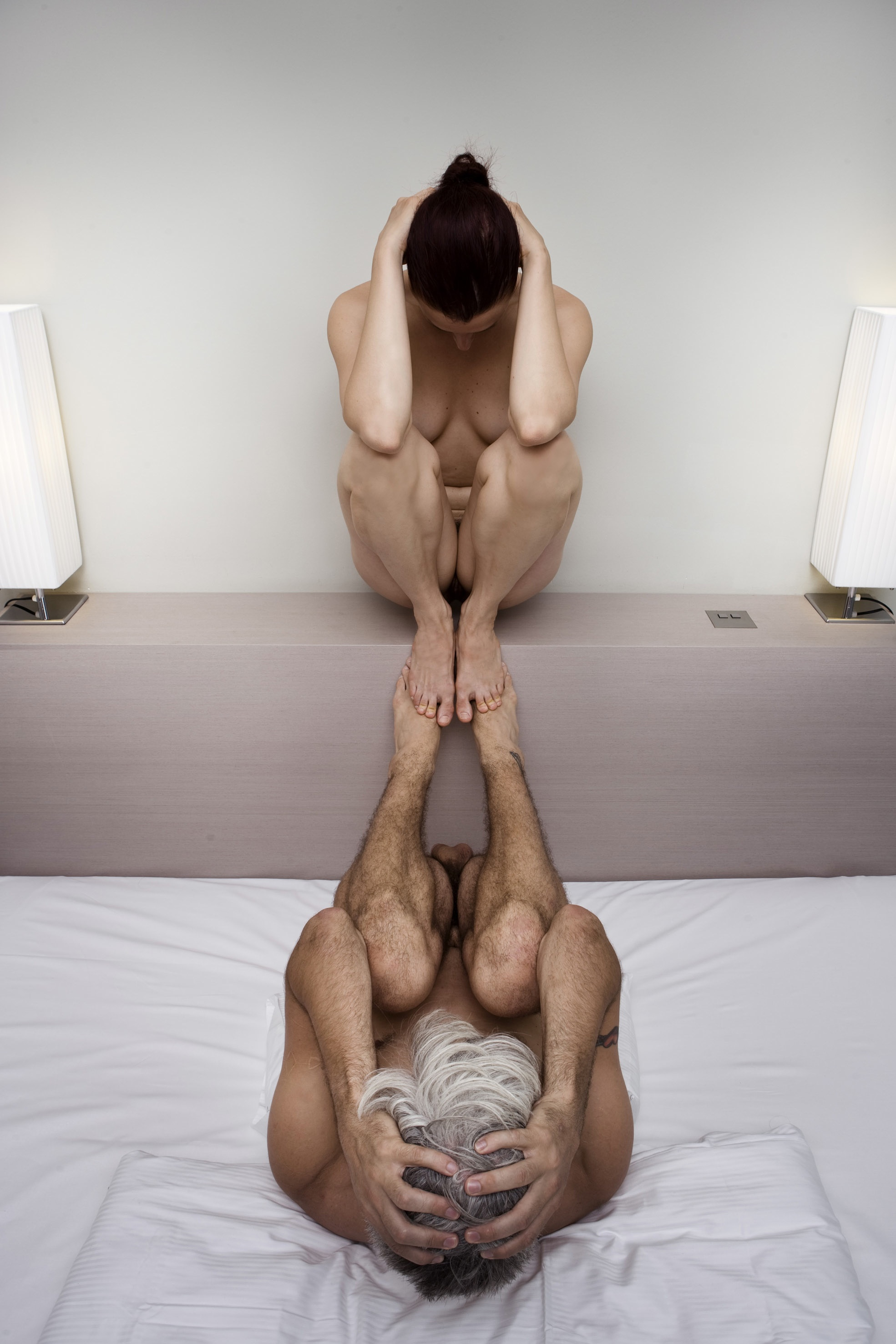 Scaroni and Curtis mirror one another, toe to toe, curled in almost-foetal position, knees to chest, elows on knees, hands on heads. (photo: Sven Hagolani)