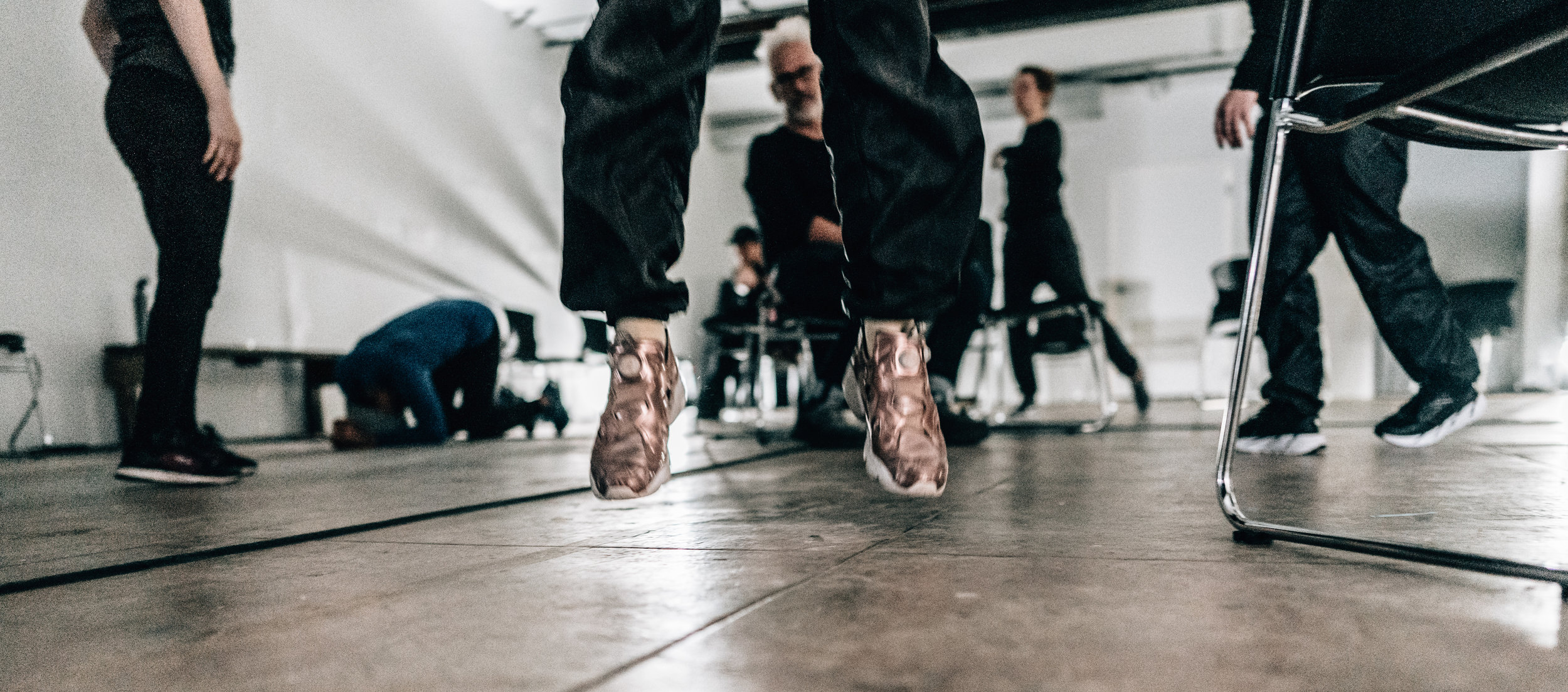 Legs in metallic pink shoes jump out of frame on concrete floor, legs apart. In background Jess Curtis looks at camera through the open legs. Others stand, crawl behind. (photo: Robbie Sweeny)