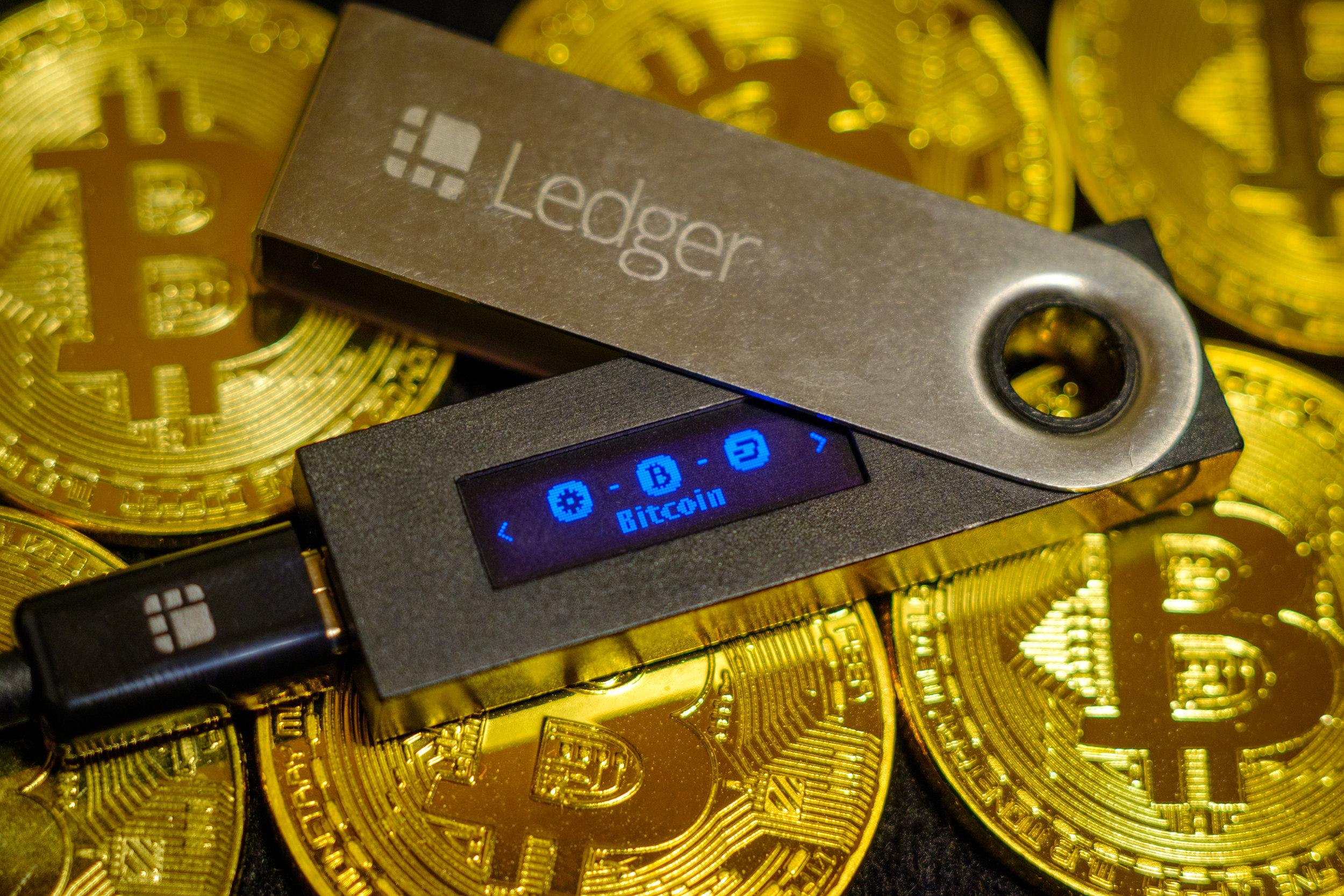 Cold crypto wallet Ledger Nano S lying on golden bitcoin coins
