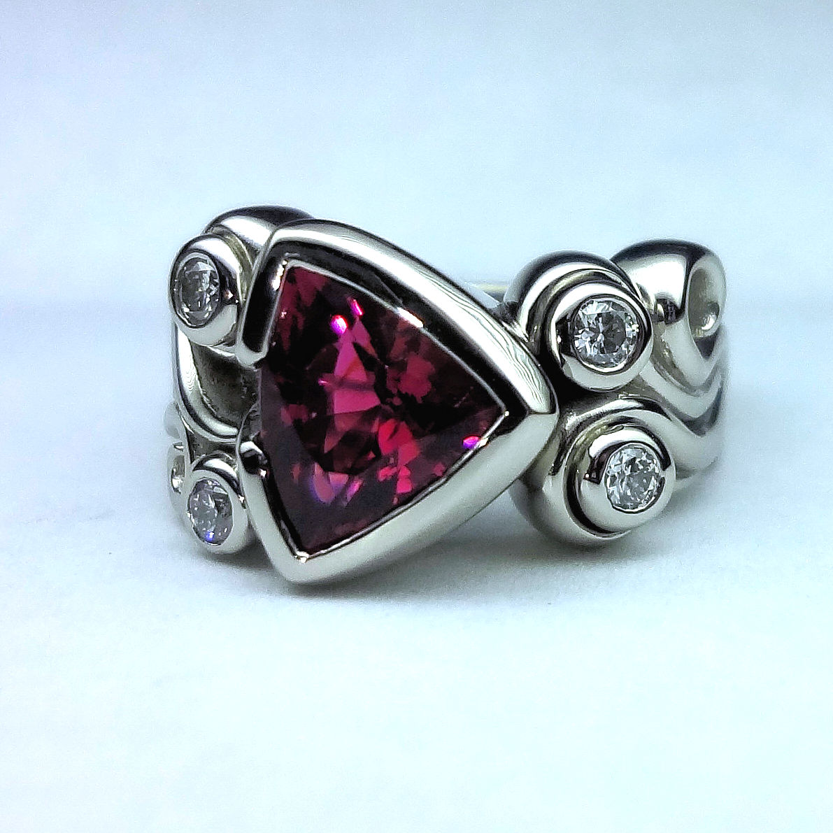 Pink Tourmaline - This pretty ring was created with a stunning trillion shaped tourmaline. Diamond accents give a little flash.#PinkTourmaline