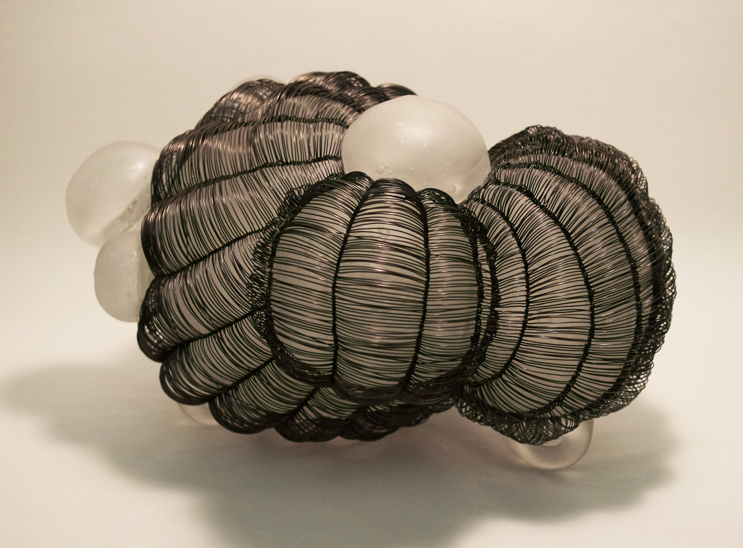 """Caged 1, side view, blown glass with woven steel wire, 8""""x11""""x13"""", 2019"""