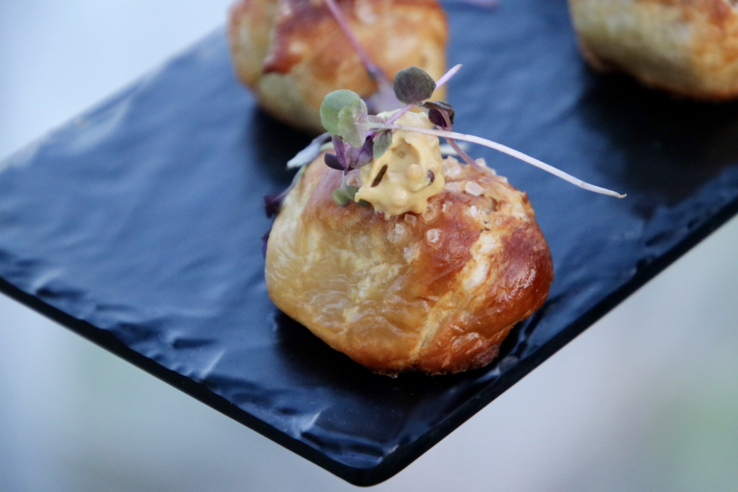 Pretzel Pigs topped with a touch of mustard and micro greens will have you rethink your ordinary pigs in a blanket.
