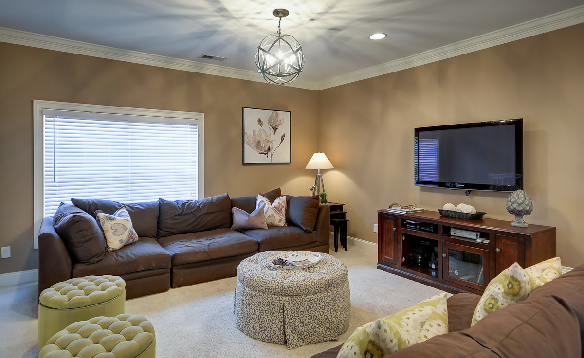New lighting, an ottoman, custom pillows and accessories immediately elevated the look of this room
