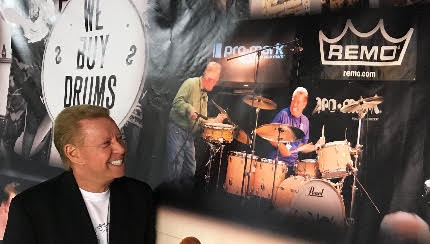 Les checks out a show banner with a photo jamming along side fellow drummer Steve Maxwell.