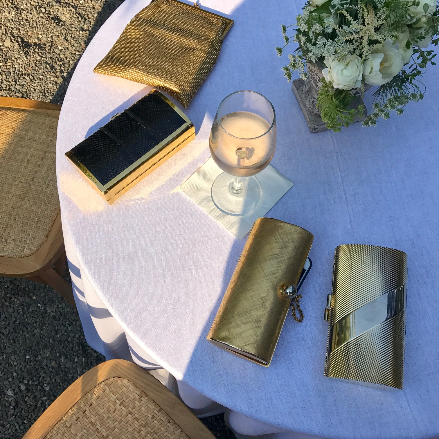 Gold clutches accompany a glass of rosé during cocktail hour in the garden.