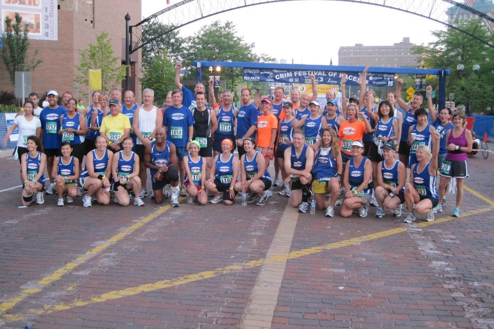 Members of the 501 Running Club line up along the Bricks of Saginaw Street for pre-race photo. Note that everyone is smiling at this point in the morning!