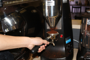 First step for the barista is to pack the coffee grounds from the coffee grinder into a metal portafilter.