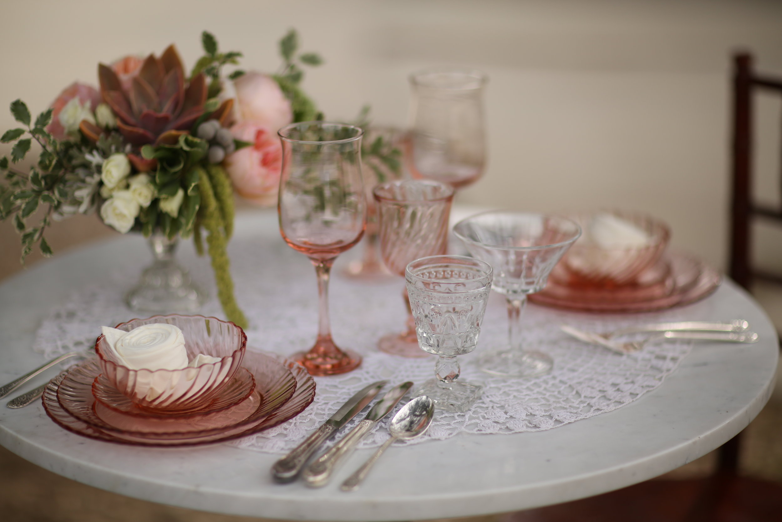 Pink Swirl vintage plates with succulent centerpiece. Vintage lace tablecloth and pink goblets. Perfect for a wedding sweetheart table. Wedding rentals in Murrieta.
