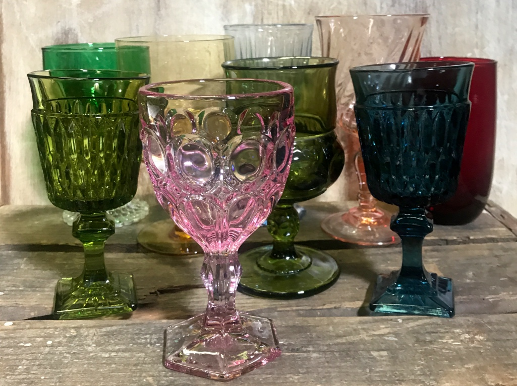 Colorful mismatched vintage glassware goblets. Amber glass, pink glass, blue glass, olive green glass, emerald glass, ruby glass, pink swirl glass. Eclectic Vintage Wedding rentals in the Temecula Valley.