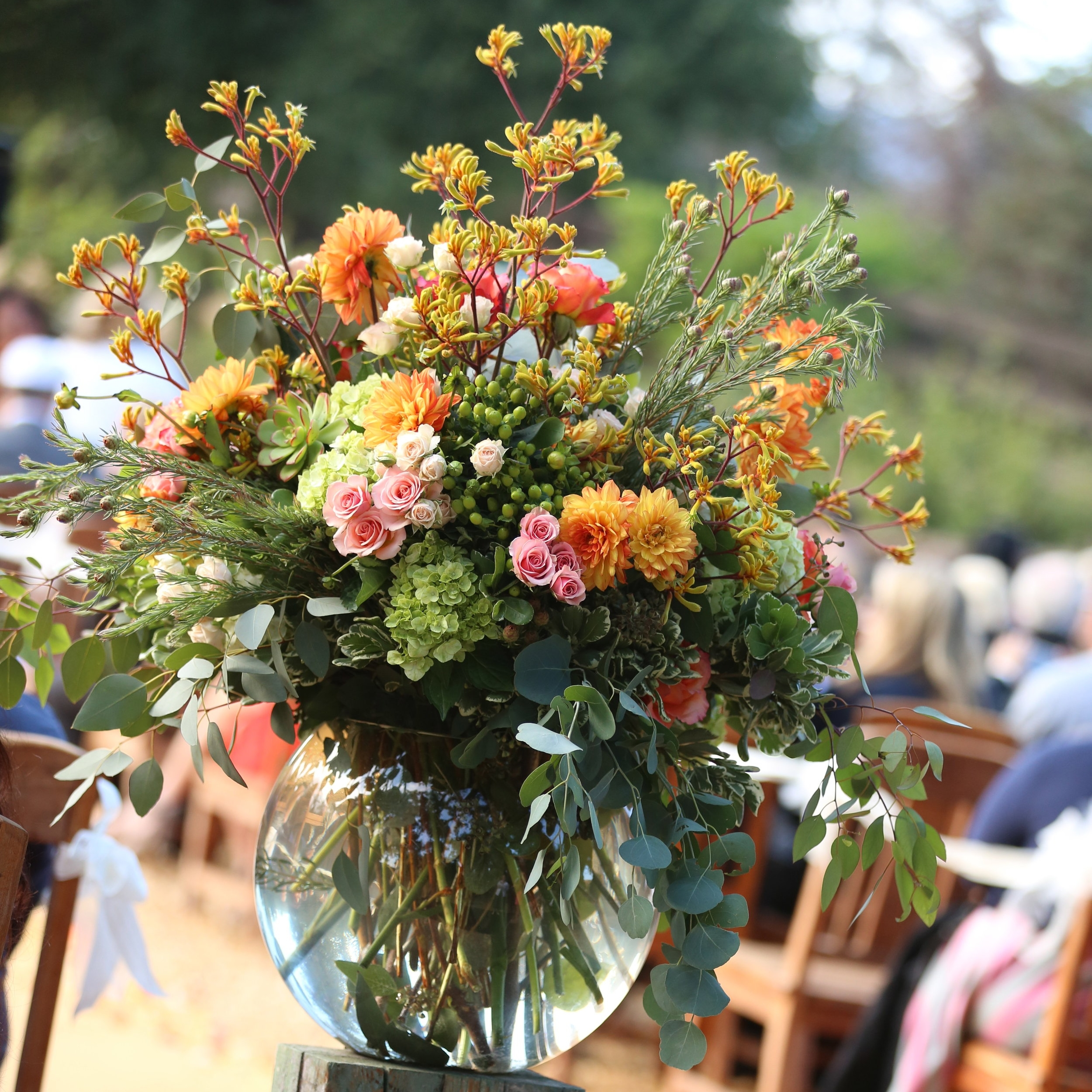 Large fish bowl vase with beautiful floral arrangements at a wedding ceremony