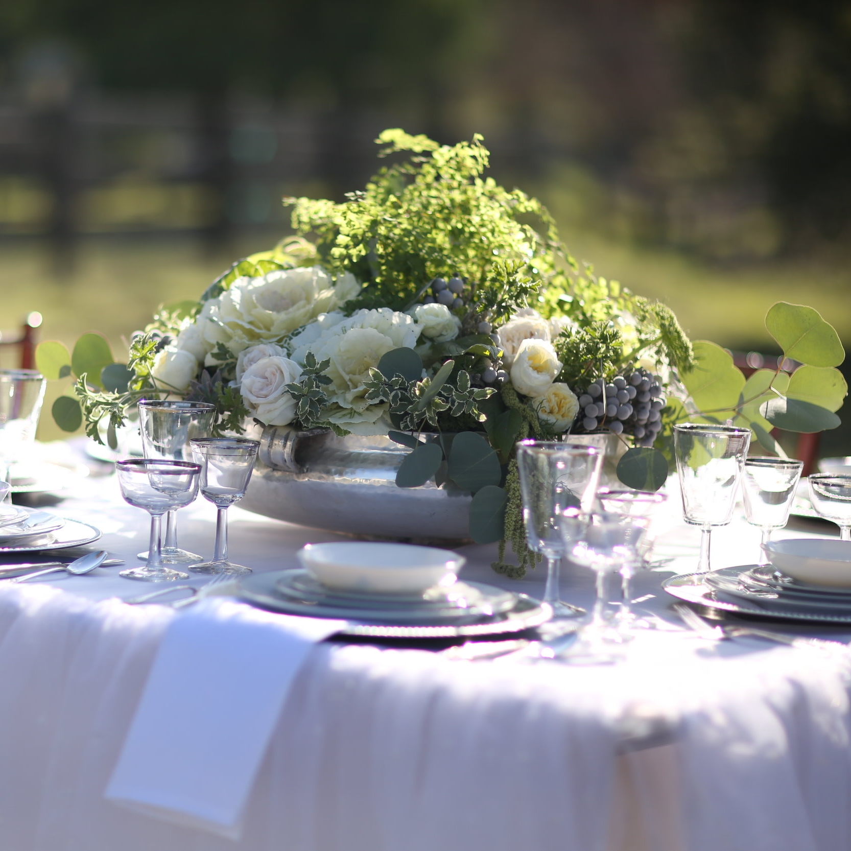 Very large round shiny silver container or floral container on wedding guest table with silver china and goblets