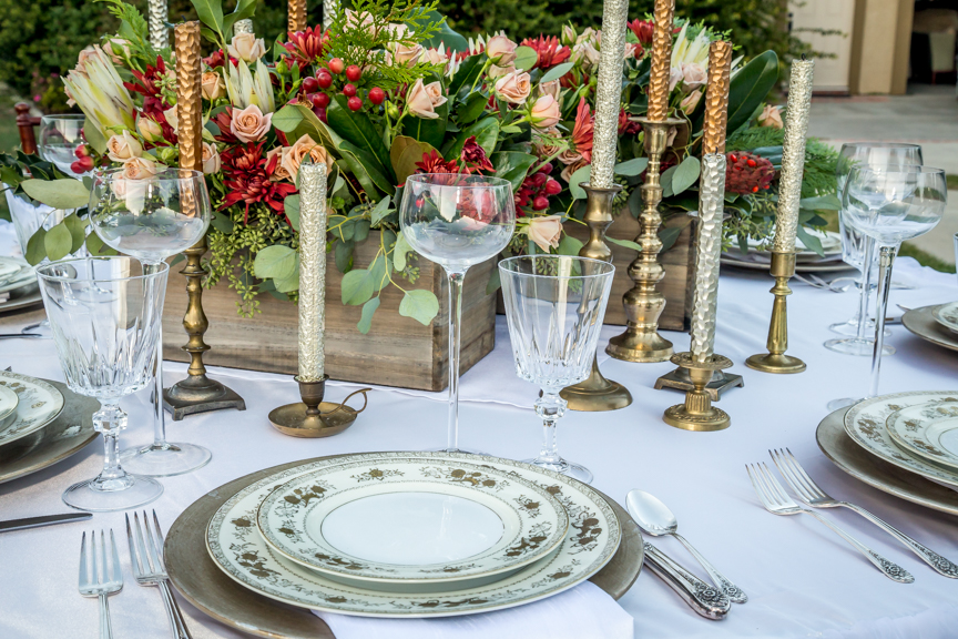 Wooden box floral centerpieces with assorted brass candlesticks. Vintage gold china with crystal goblets, and gold chargers. Silver plate utensils.