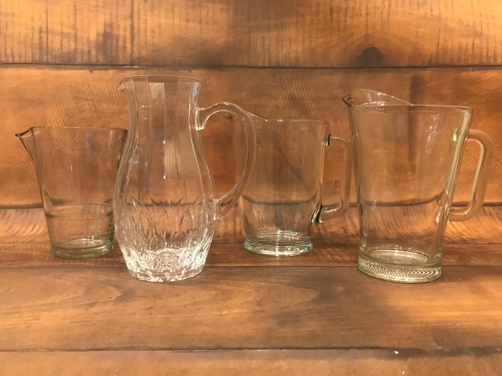 vintage mismatched cut glass and clear water pitchers.