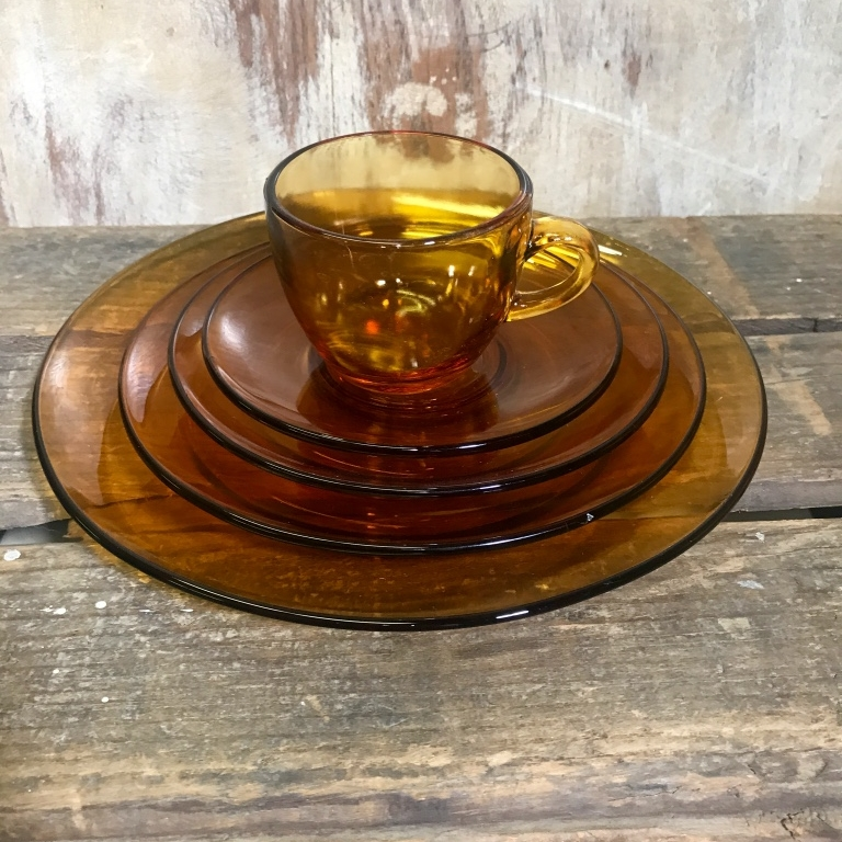 Full place setting of amber depression glass. Dinner Plate, salad plate, bread plate, cup and saucer. Mid Century Modern wedding rentals in the Temecula Valley.