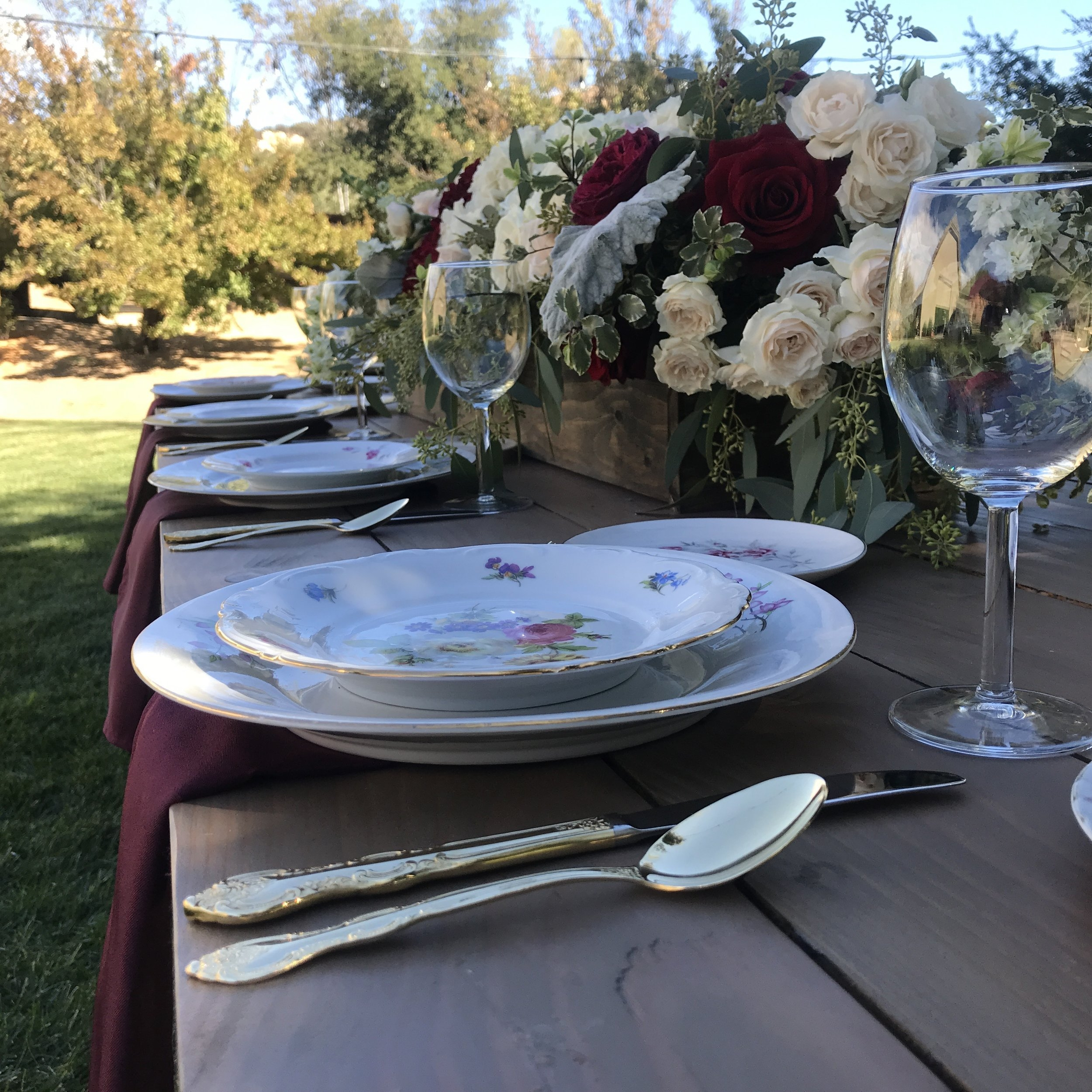 Close up of pink vintage china with red wine goblets and gold silverware. Large floral arrangement in a wooden planter box with beautiful pink roses. Temecula Valley rentals.