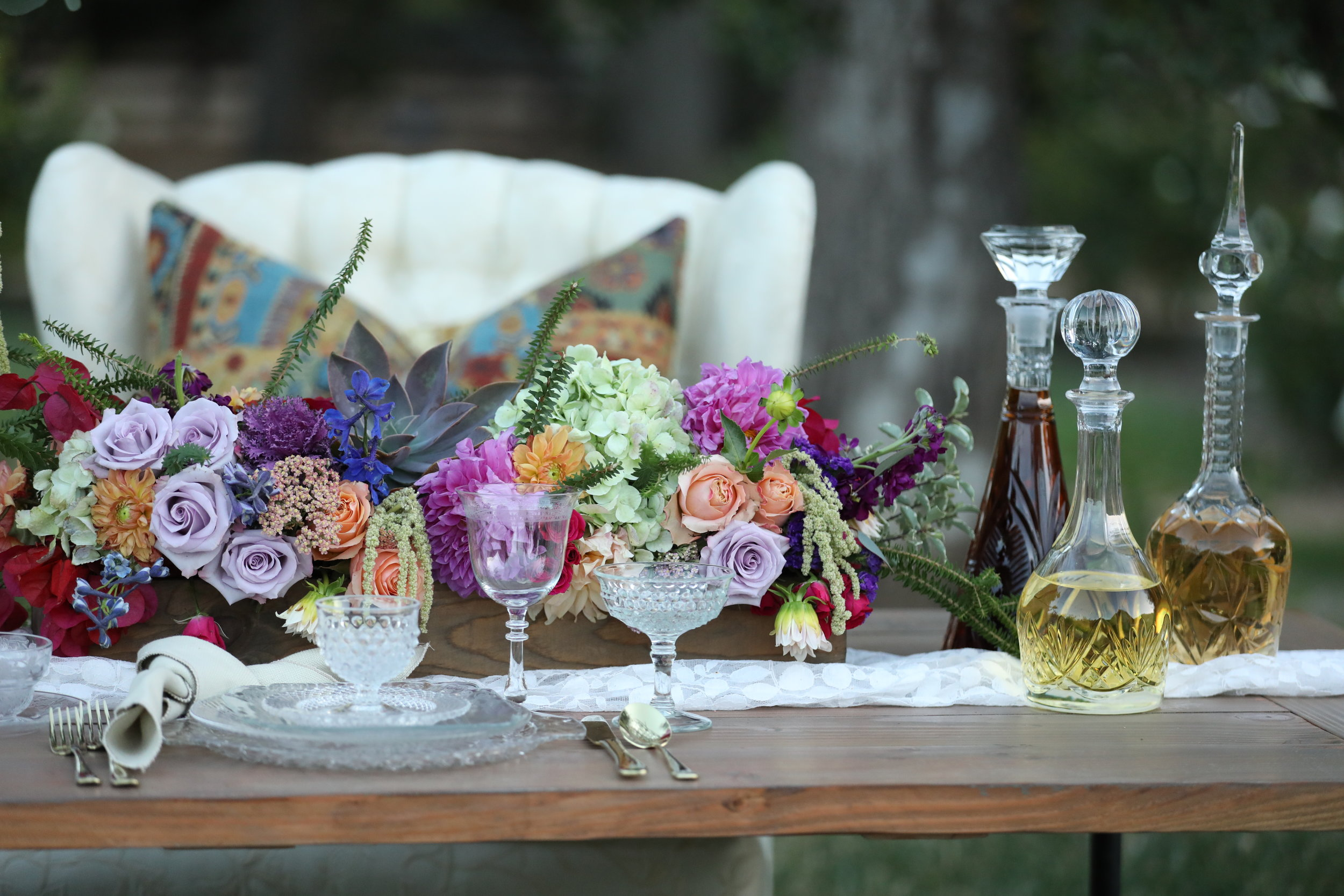 Boho setting with an industrial farm table and cut glass dishes. Vintage decanters and spring floral centerpiece. Wedding rentals in the Temecula Valley and Murrieta.