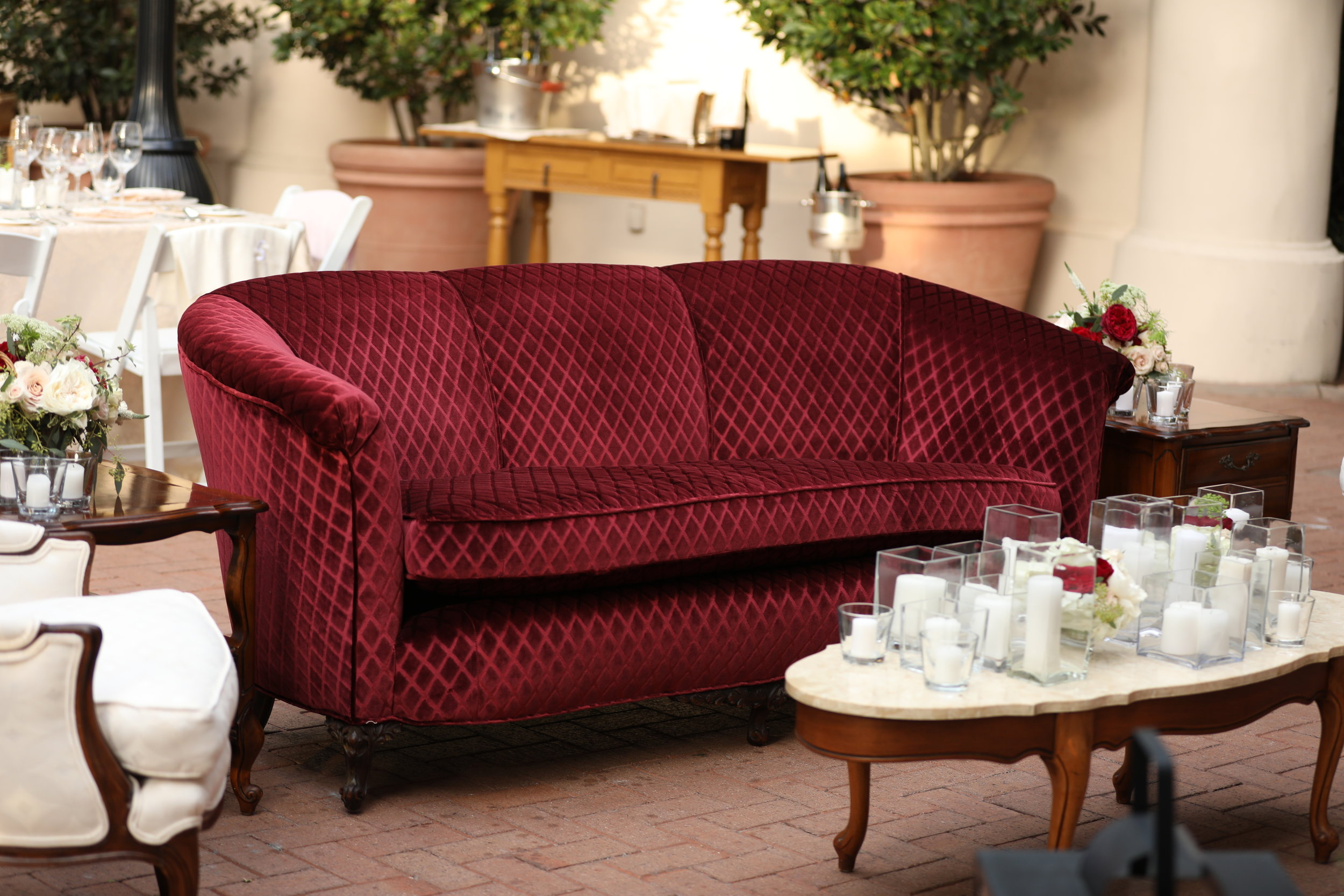 Vintage velvet Marsala couch with coffee table and pillar candles at a reception at Pelican Hill in Orange County, California.