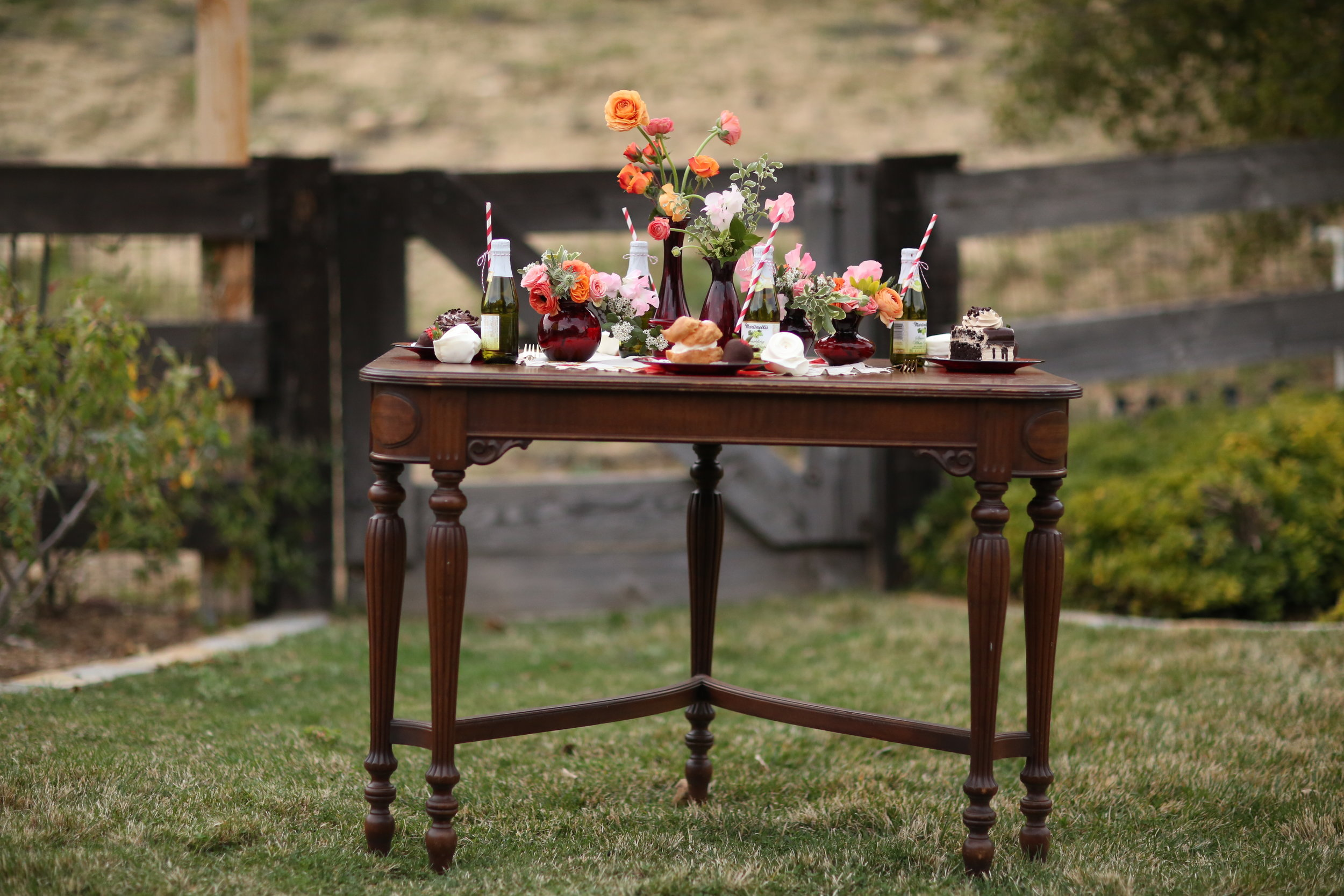 vintage oak dining table with spindle legs. Ruby glass vases and dessert plates with french pastries.