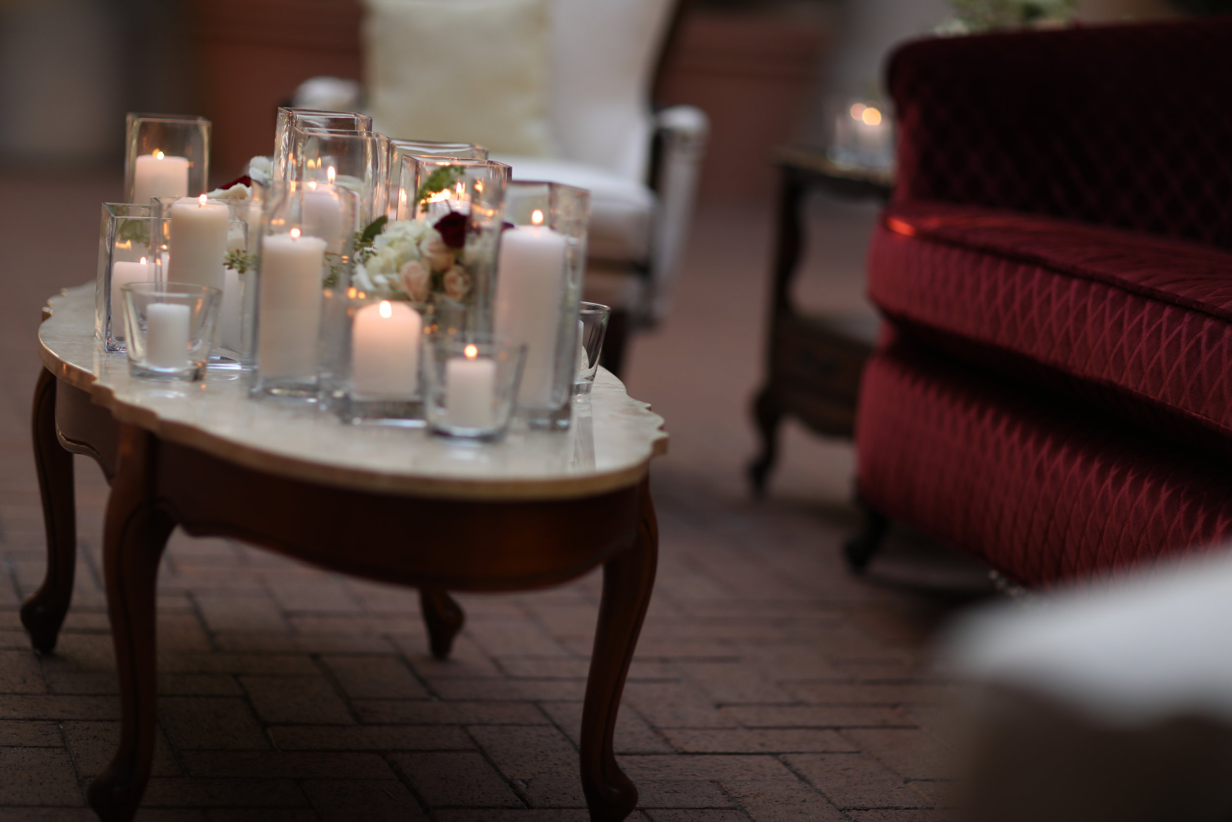 wooden coffee table with decorative scroll legs and a granite top with a scalloped edge. Square vases, cylinder vases, votives, and floral on top of the table. Sitting area at Pelican Hill wedding