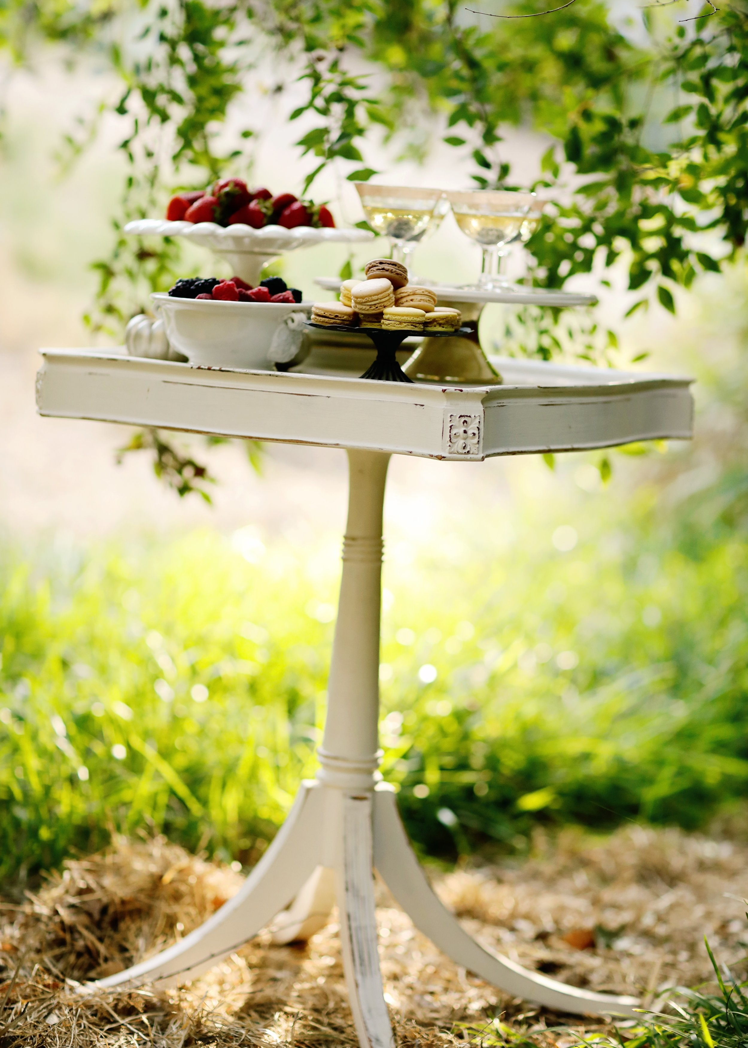 Distressed white square accent table with flared pedestal legs topped with assorted dishes.