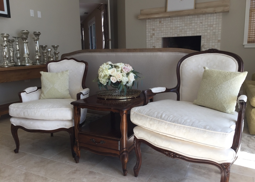 Two cream colored Bergere chairs with a side table with a shelve. Floral arrangement on top of a vintage brass mirror. Mercury glass candlesticks