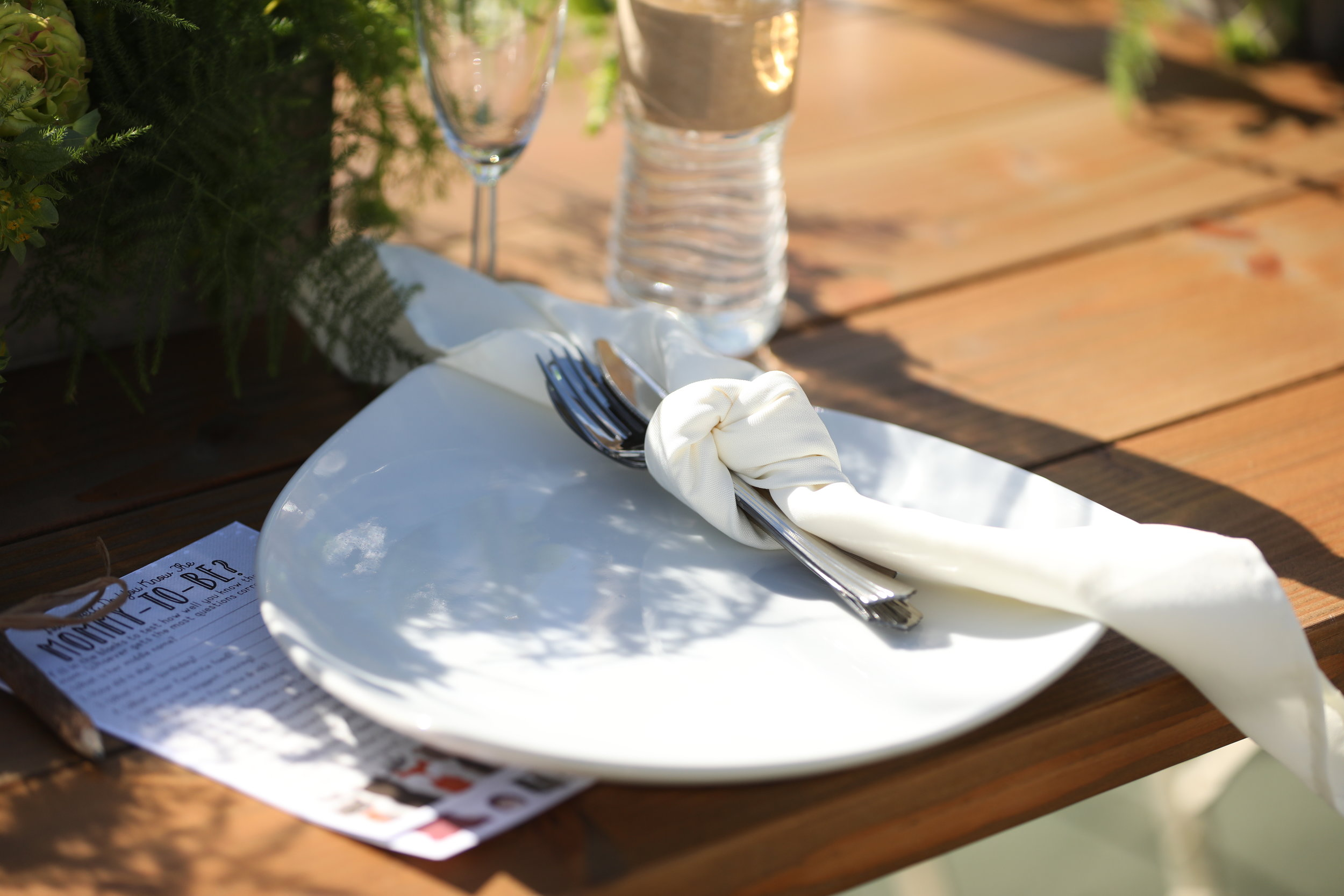 Modern white triangle plate with cream napkin and silverware on a farm table at a baby shower. Event rental in the Temecula Valley.