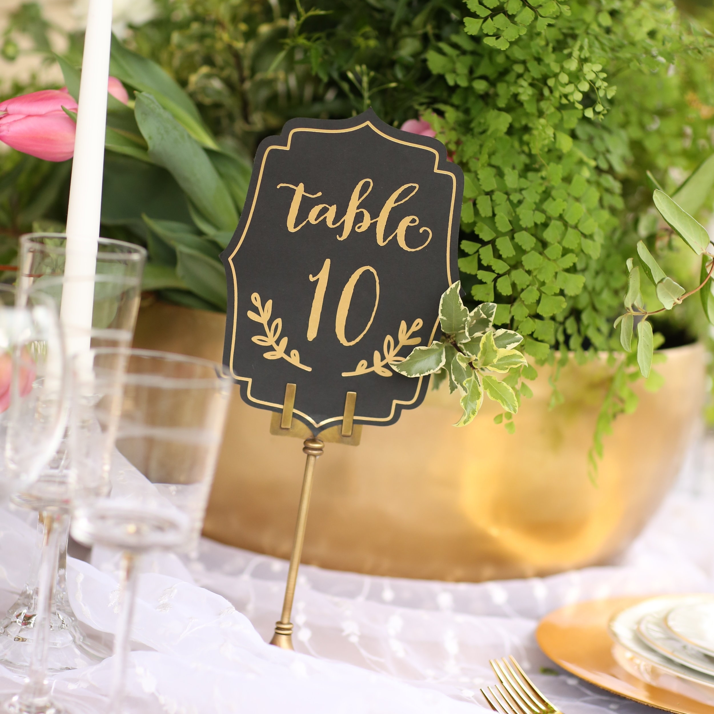 Gold round heavy brass bowls with greenery floral centerpiece. Table number holder.