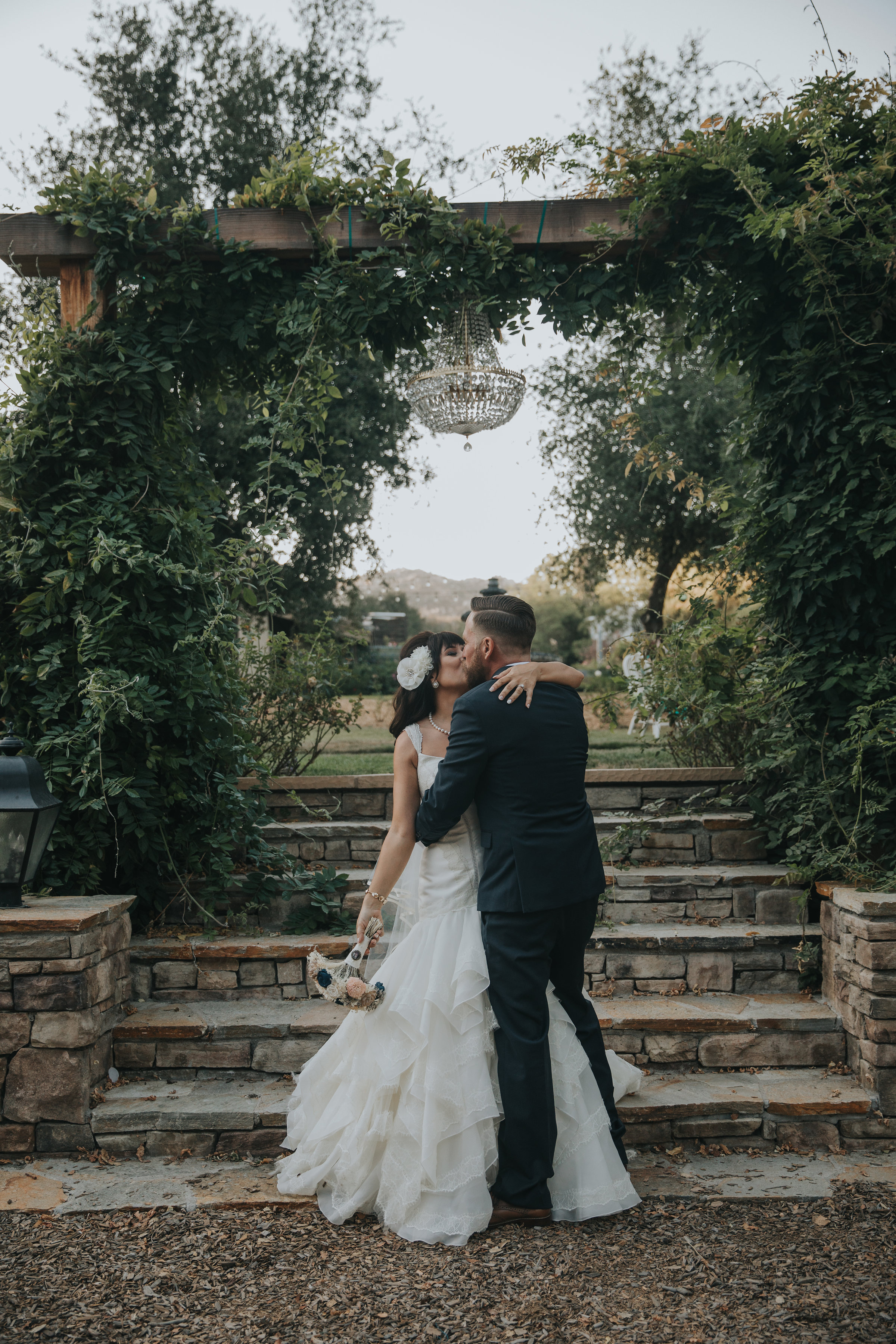 Bride and groom kissing under a wisteria arch at Chateau Adare in the Temecula Valley.