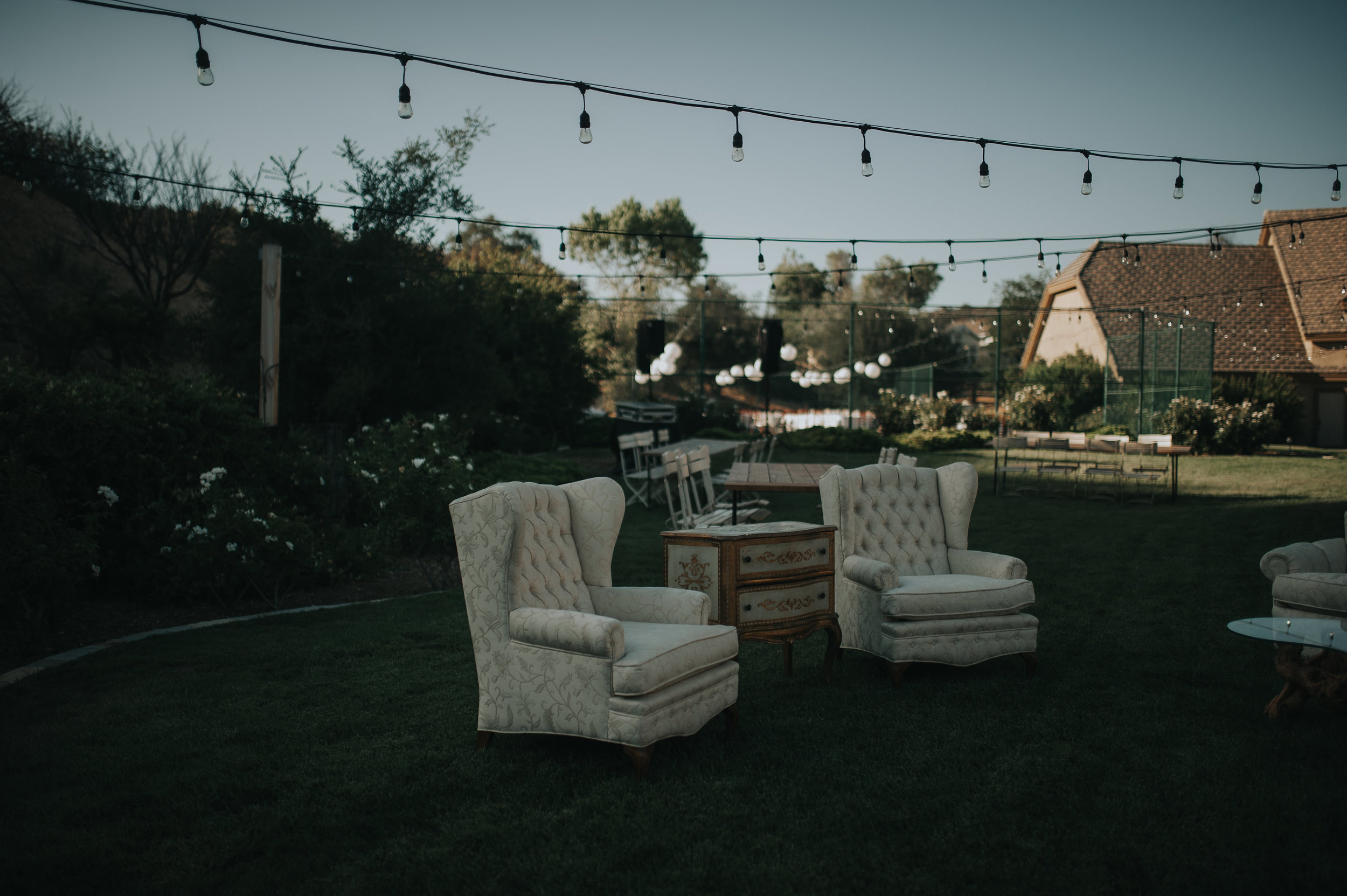 Cream over stuffed chairs and a French gold leafed dresser at a wedding reception in the Temecula Valley. Vintage rental furniture.
