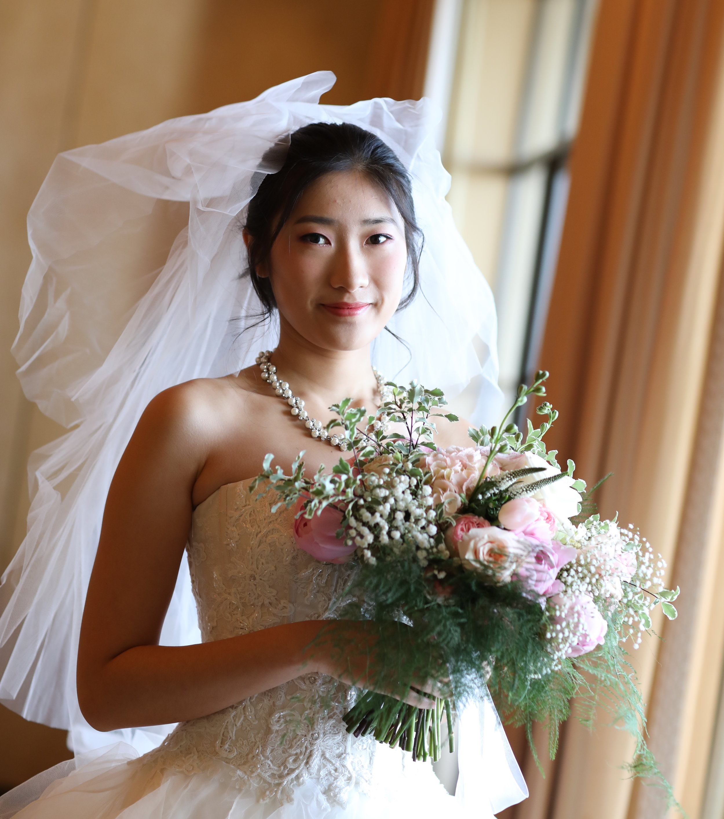 Chinese Bride in a designer wedding dress holding a pink floral bridal bouquet at the Resort at Pelican Hill.