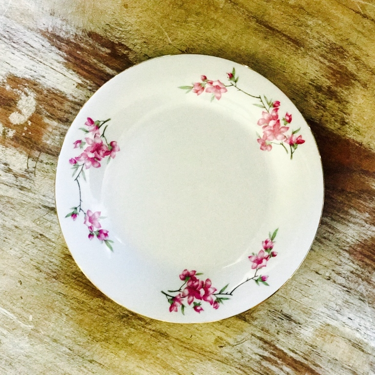 Mismatched fine china bread or appetizer plate. Pink floral pattern. For Rent.