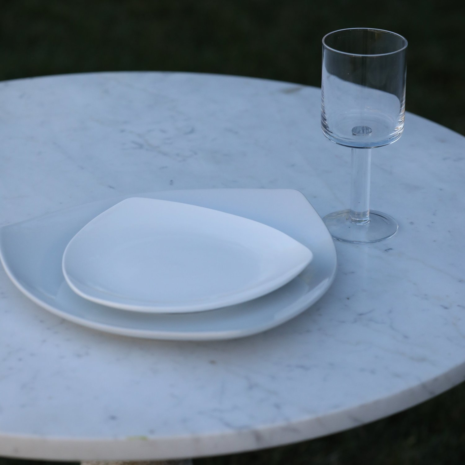 White triangle contemporary table setting with square goblet on marble round table. All items available to rent in Murrieta, part of the Temecula Valley.