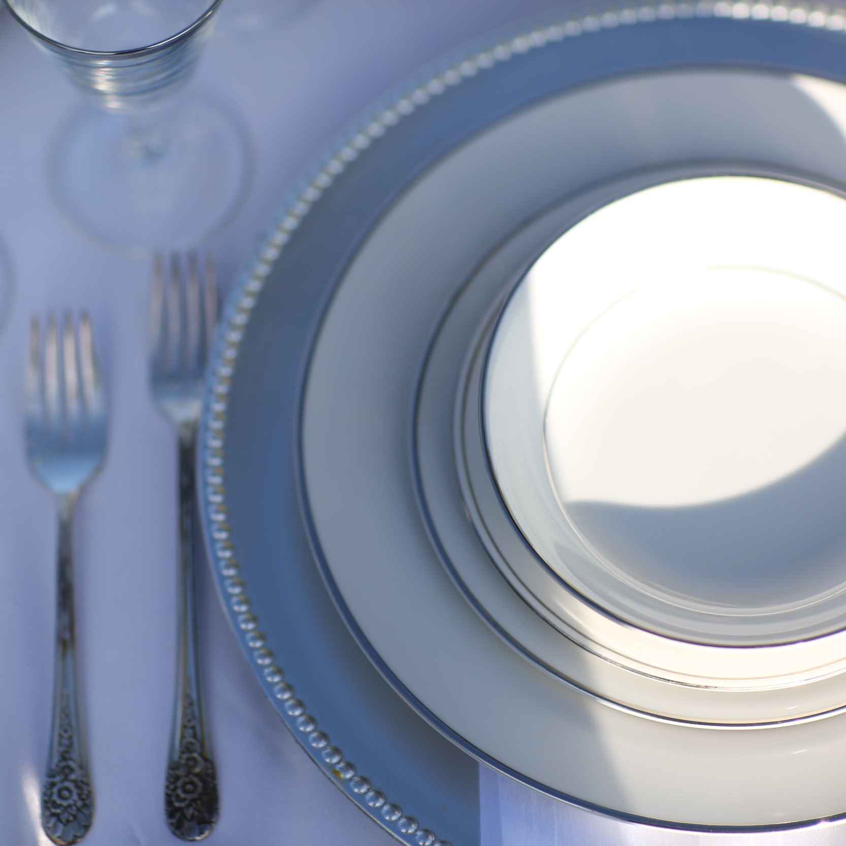 Silver acrylic charger place setting with silver rimmed china plates. Wedding rentals in the Temecula Valley.