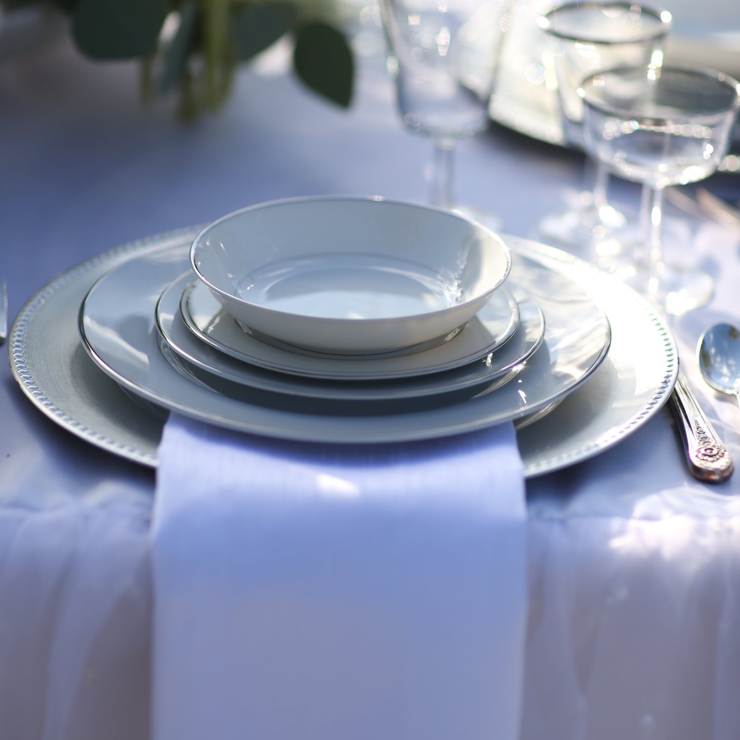 Acrylic beaded charger plates with silver rimmed china place setting on wedding table. Rentals.