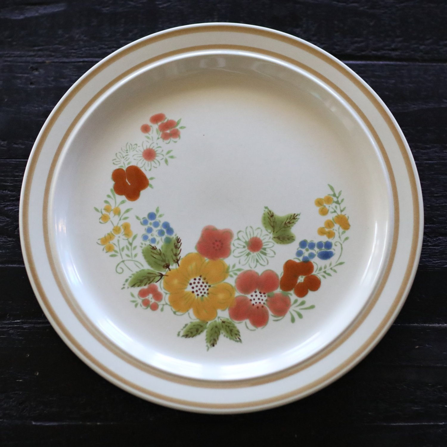 Vintage mismatched assorted stoneware with rust and orange flowers. Wedding rentals.