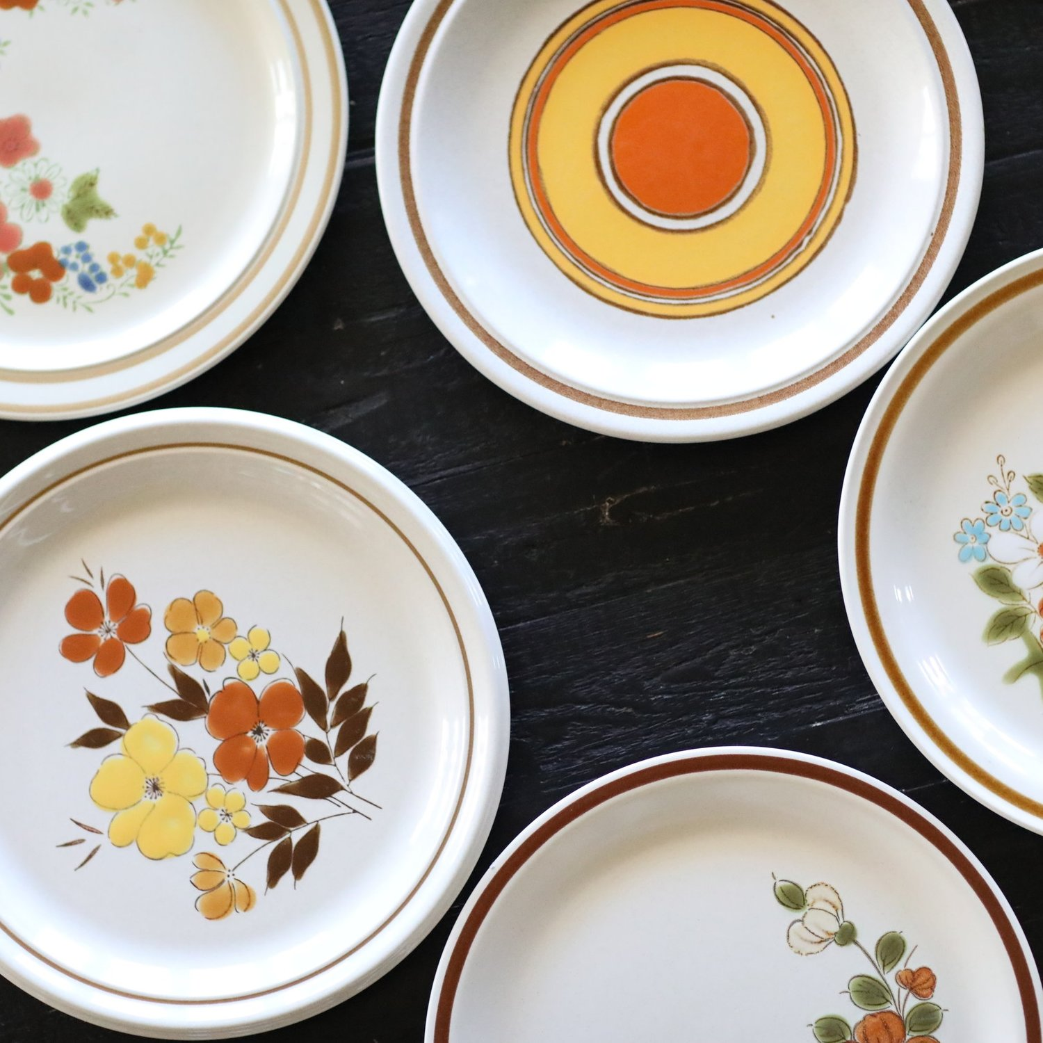 Assorted vintage mismatched stoneware in yellows and oranges. Event rentals.