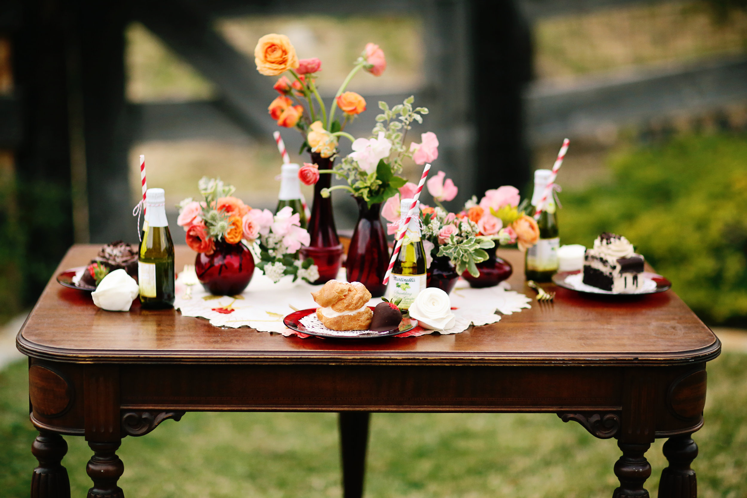 A vintage table topped with ruby glass details. Ruby glass dessert plates with assorted desserts. Ruby glass vases with colorful flowers. All for rent in Murrieta.
