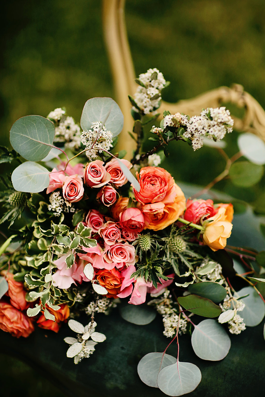 Bridal bouquet feating pink spray roses, orange ranunculus, lots of greenery and a little thistle. A colorful wedding palette for a styled shoot in Murrieta.