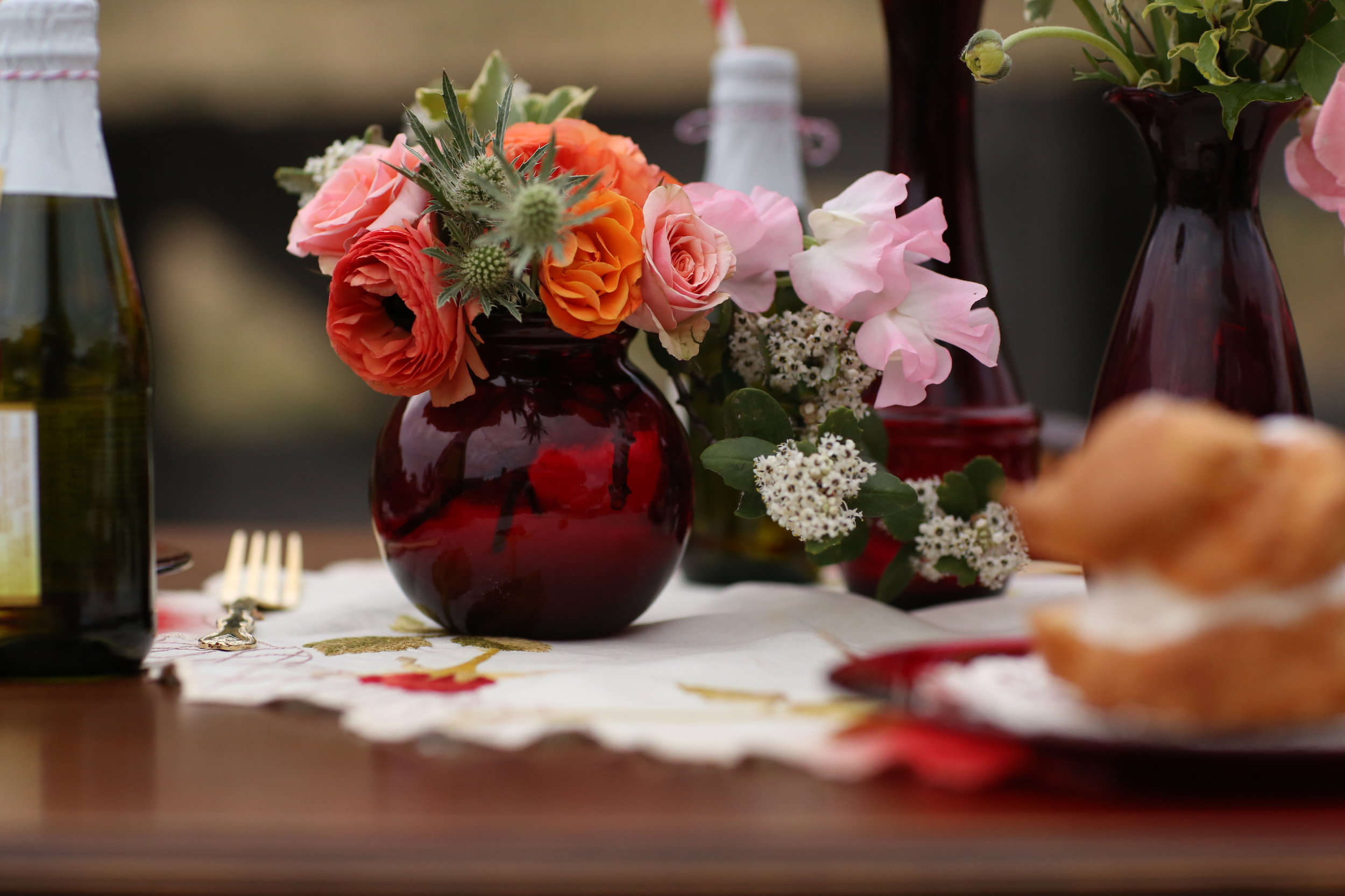 Styled shoot featuring orange, red, pink and green for the colors. Anchor Hocking Ruby Red vases went perfect on the vintage table. All available to rent in the Temecula Valley.