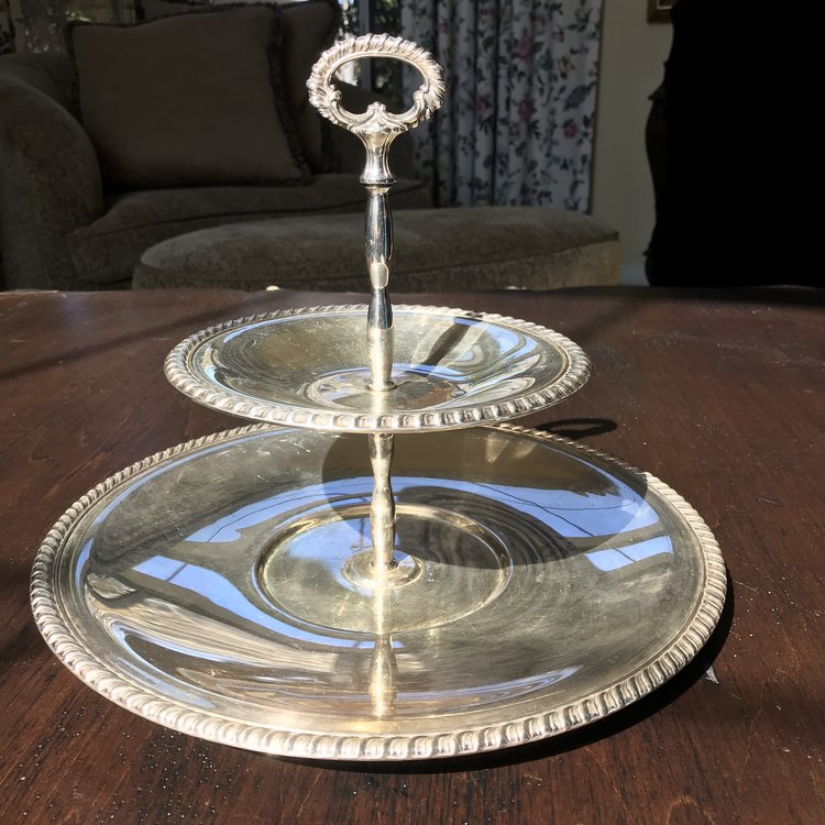 "Silver Two Tiered Tray    Vintage silver plate two tiered tray with decorative handle and rope edge. 8"" tall x 12.5"" bottom, 7.5"" top"