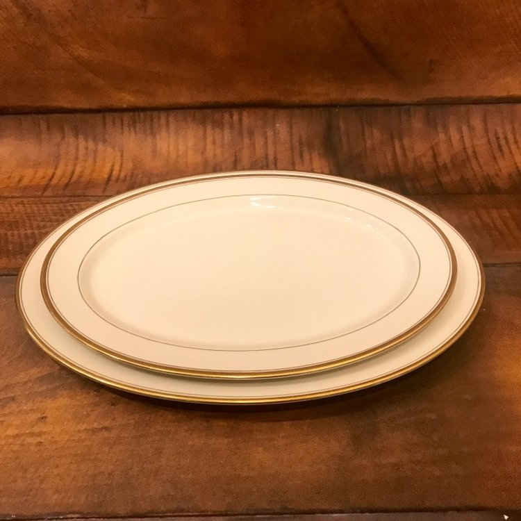 Mismatched vintage china platters with gold rim.