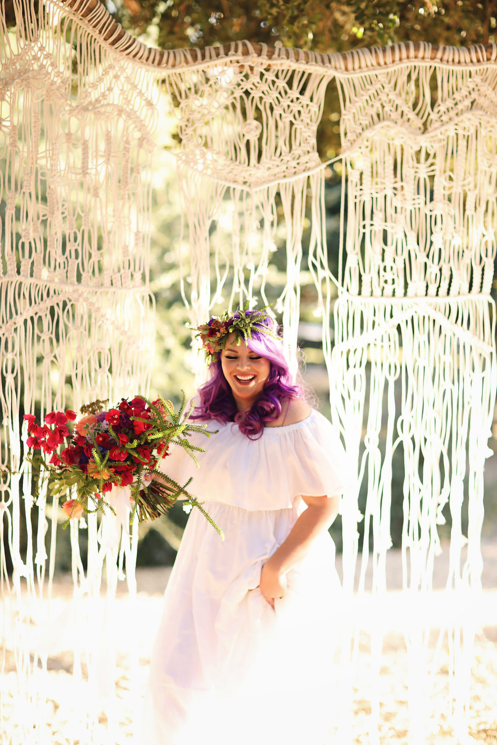 Laughing ultra violet hair bride in front of hand created macrame backdrop.