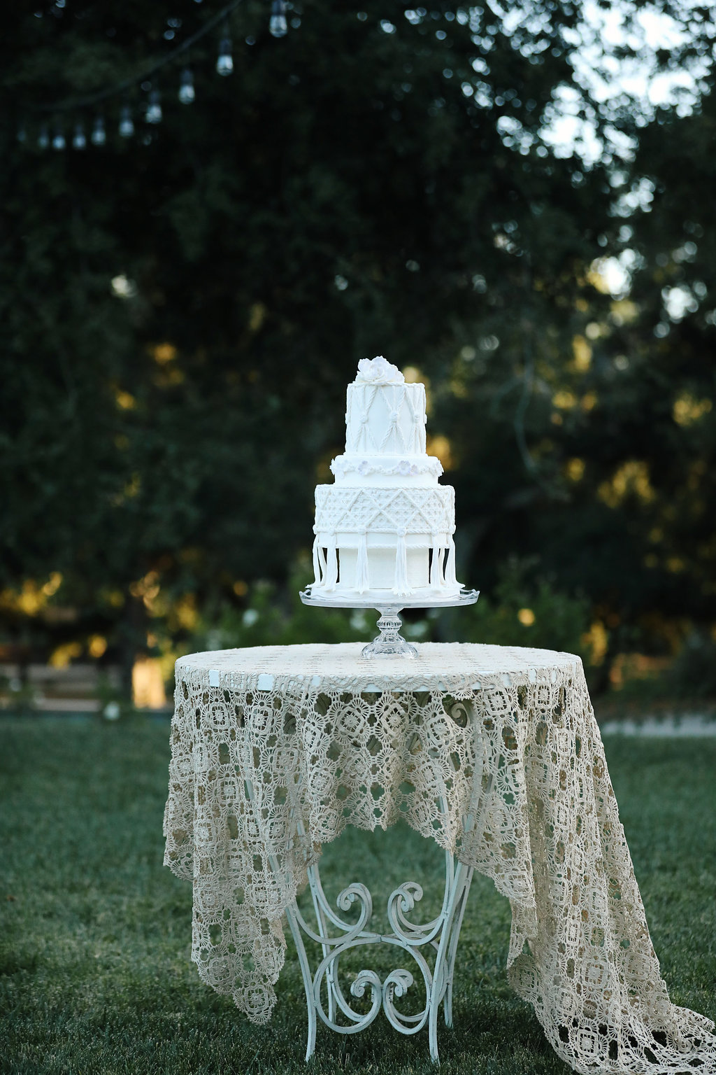 Macrame wedding cake by Susan Carberry on top of vintage lace table cloth and wrought iron table. All vintage rentals from Birdie in a Barn in the Temecula Valley.