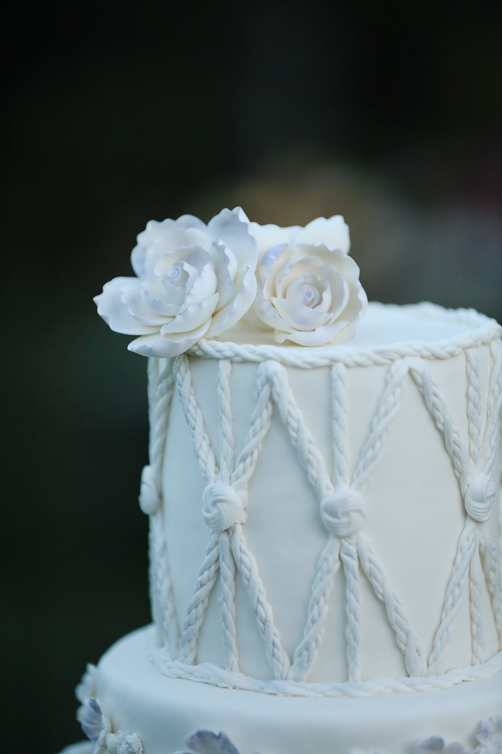 Close up details of the macrame wedding cake with gum paste flowers.