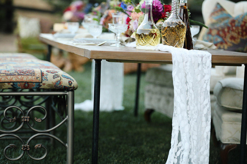 Industrial Farm tables with tufted off white chairs and boho upholstery iron benches. Vintage rentals in the Temecula Valley.