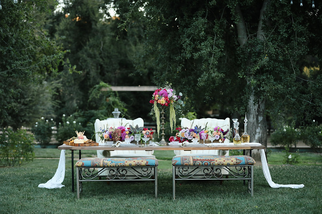 Bohemian wedding table with iron benches and tufted chairs. Vintage rentals.