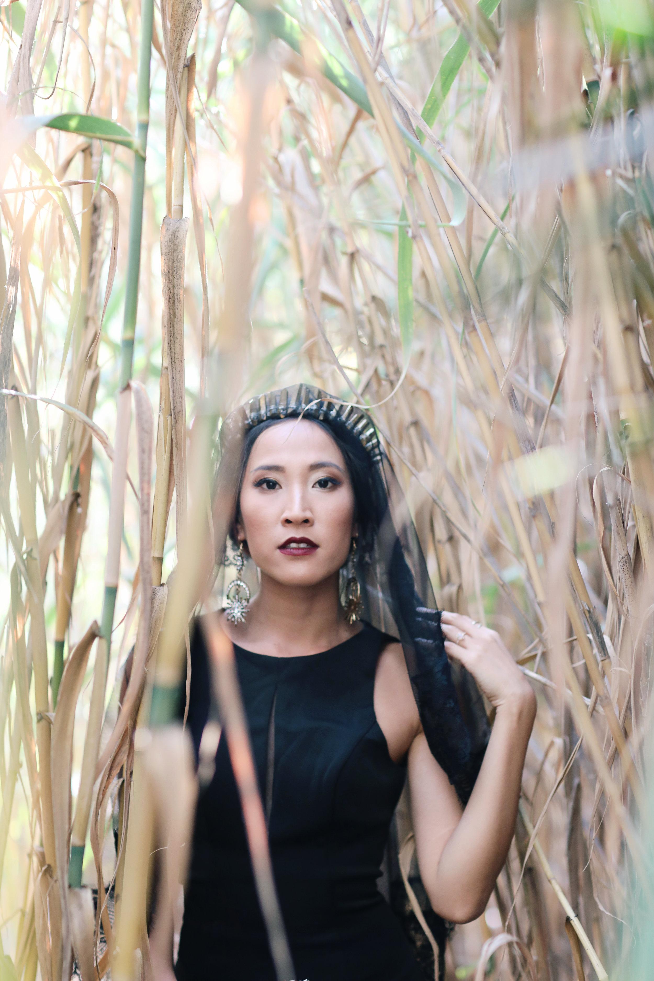 Bride in a black wedding dress in the reeds in Orange County.