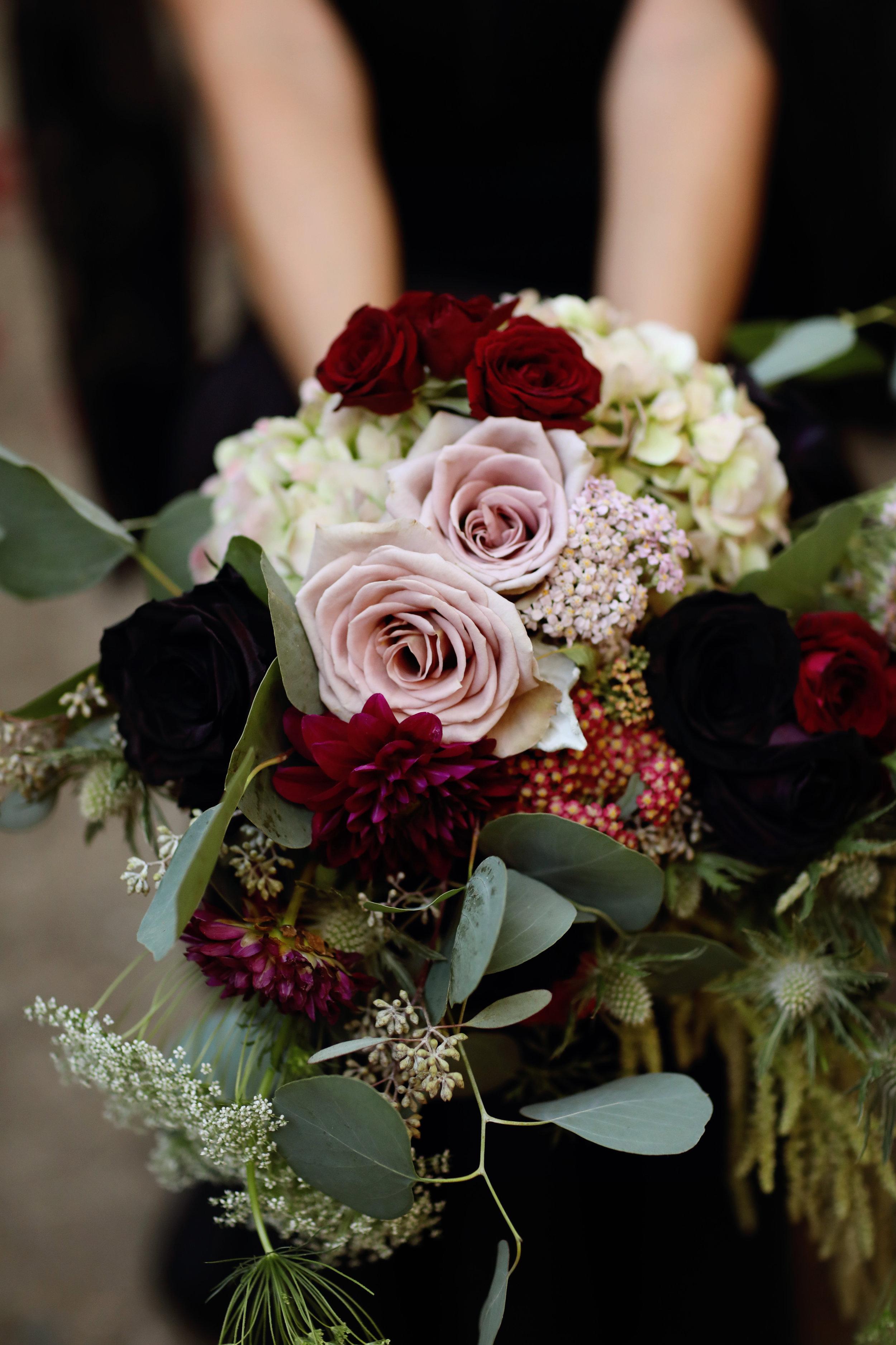 Brides bouquet Sith black dahlias, thistle, roses, and seeded eucalyptus