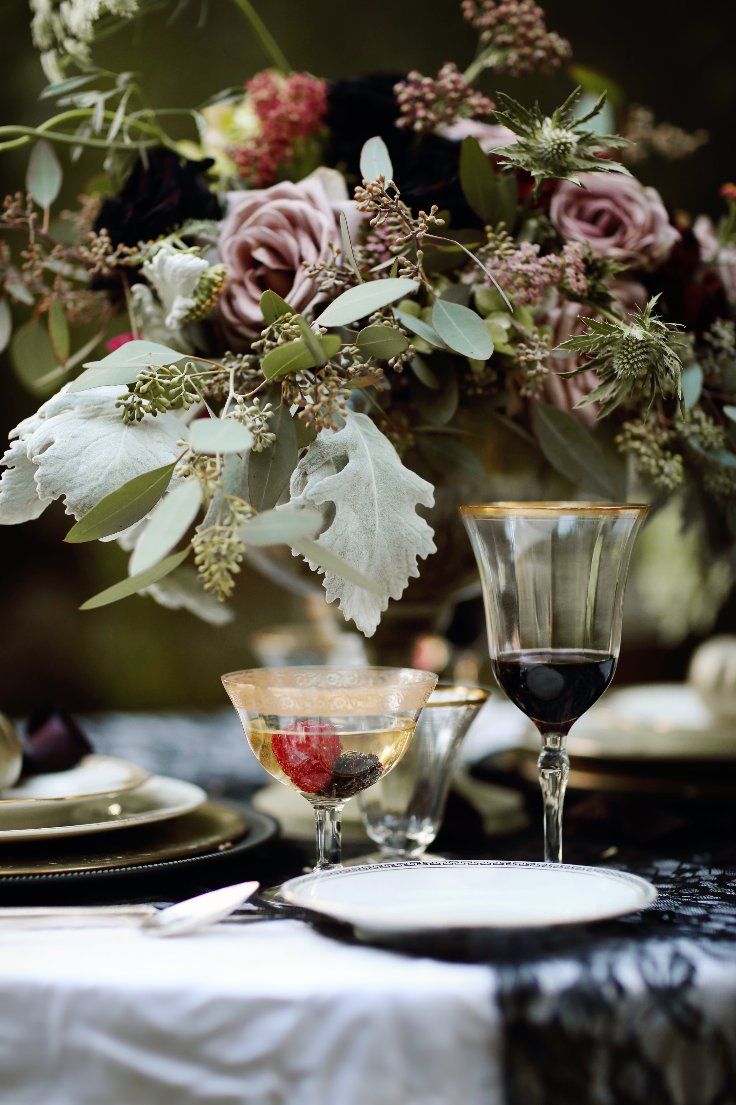 Black Dahlia centerpiece at a wedding table. Gold rimmed goblets and gold china table settings from Birdie in a Barn.